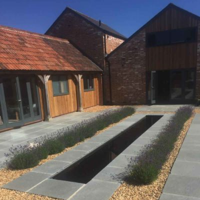 barn conversion with patio area and square pond