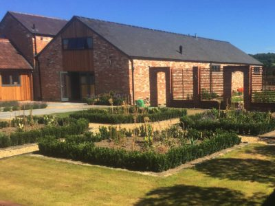 Garden Design with square beds in front of barn